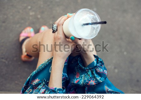 Girl with glasses drinking milkshake. Outdoor lifestyle portrait of woman - stock photo