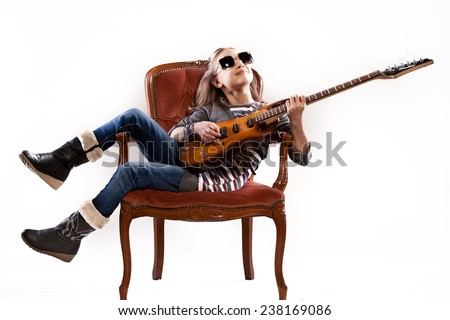 girl with guitar and sunglasses playing as a rockstar - stock photo