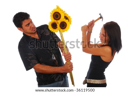 Girl with Hammer beating a guy with flowers - stock photo