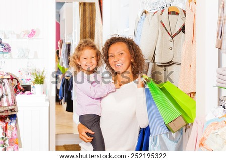 Girl with happy mother holding bags while shopping - stock photo