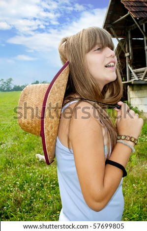 Girl with hat on the meadow - stock photo
