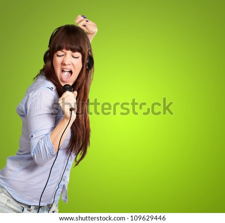 Girl With Headphone Singing On Mike On Green Background - stock photo