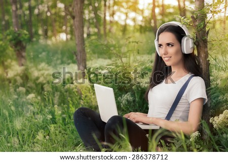 Girl with Headphones and Laptop in - Portrait of a young woman smiling and listening to music