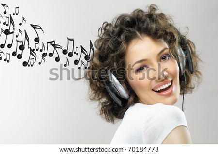 girl with headphones on the grey background - stock photo