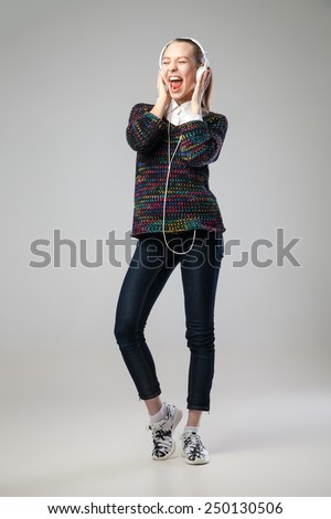 Girl With Headphones Singing and Dancing  On grey Background. Full length portrait. - stock photo
