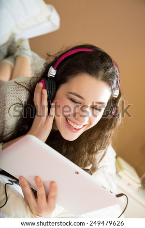 Girl with headphones watching something funny in her tablet lying in bed - stock photo
