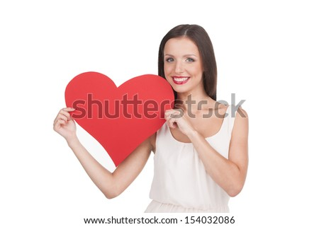 Girl with heart. Attractive young woman holding paper heart and smiling while isolated on white