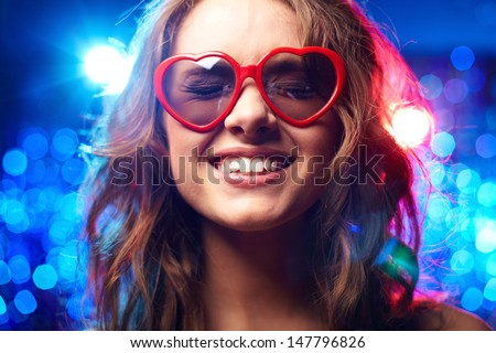 Girl with heart-shaped glasses and closed eyes smiling - stock photo