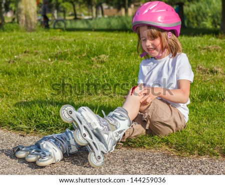 Girl with helmet on but without protective knee pads crying - stock photo
