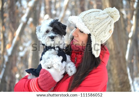 Girl with her cute little dog in the winter forest - stock photo
