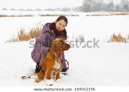 Girl with her dog in snow in the park in winter