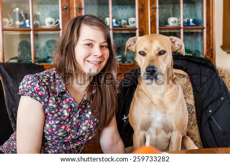 Girl with her dog sitting next each other - stock photo