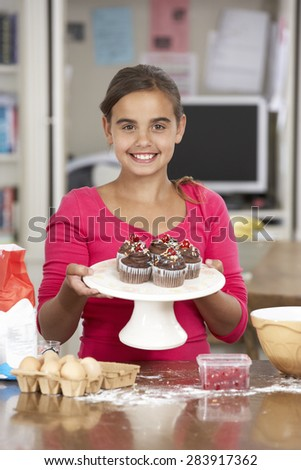 Girl With Homemade Cupcakes In Kitchen - stock photo