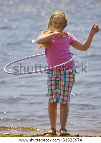 Girl with hula hoop on beach in a tight shot - stock photo