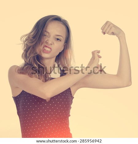 Girl with imaginary biceps - stock photo
