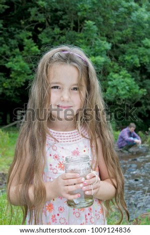 Girl with jam jar by the river