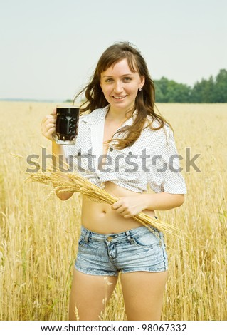 Girl  with kvass at cereals field in summer - stock photo