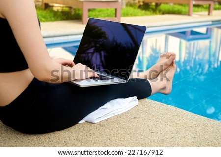 Girl with Laptop by the pool, working on vacation with mobility concept - stock photo