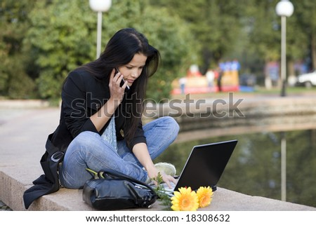 Girl with laptop in park - stock photo