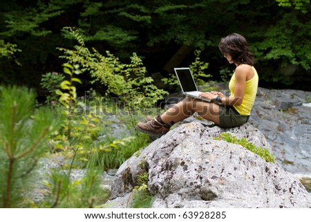 Girl with Laptop, Sitting On a Rock,  In the Forest - stock photo