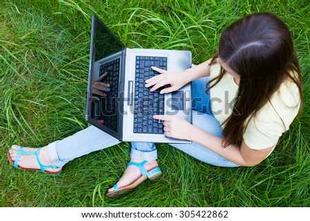 Girl with laptop sitting on green grass