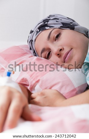 Girl with leukaemia lying in hospital bed - stock photo
