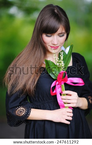 girl with lilies of the valley in the spring. - stock photo