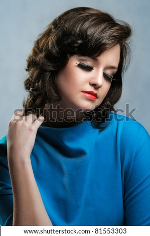 Girl with long false eyelashes in blue dress with dreamy expression - stock photo