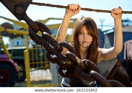 girl with long hair at sunset, young girl among large metallic chains