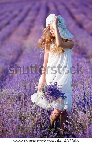 Girl with long hair collects lavender - stock photo