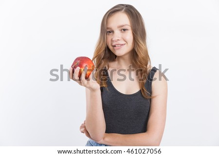 Girl with long hair in blue jeans holding red apple and smiling to camera. Concept of natural food. Portrait. Isolated