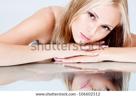 girl with long hair lying on a mirror - stock photo