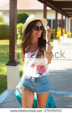 Girl with luggage at the international airport.tanned girl with large suitcases waiting for departure.Summer cool sunglasses,map,bright summer clothes colors,denim shorts,amazed,vintage teenage style  - stock photo