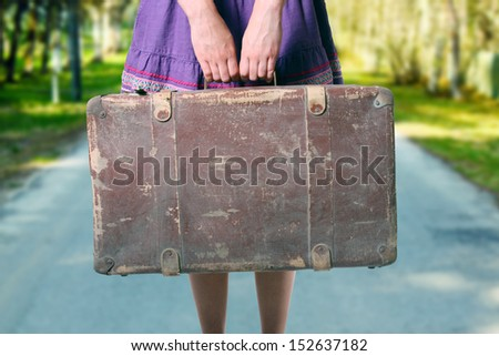 girl with luggage on the road - stock photo
