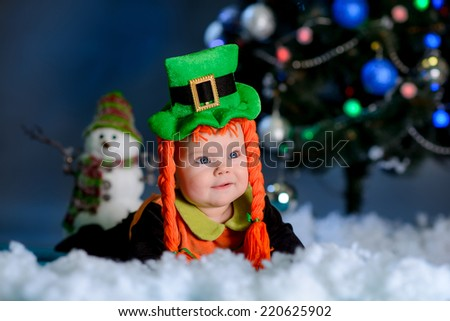 girl with lying on the carpet snow. Christmas tree in the background. smiles elf costume - stock photo