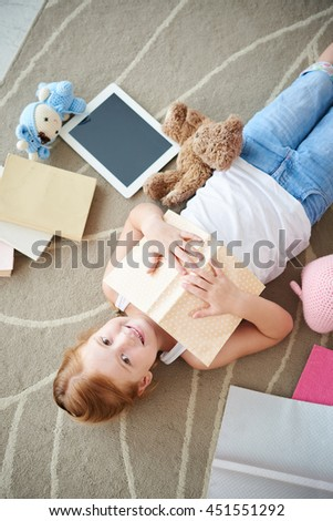 Girl with many books around lying on the floor