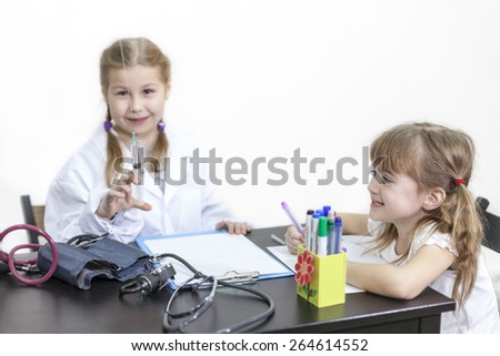 Girl with medical syringe in hands in a white coat, doctor and patient, white background - stock photo