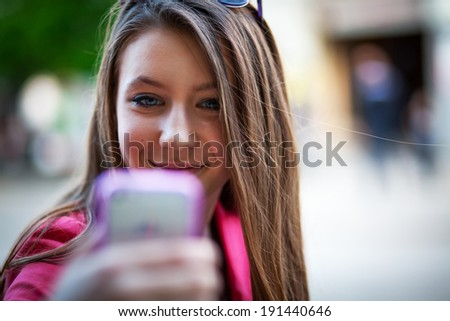 Girl with mobile phone taking photo of herself - stock photo