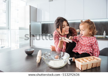 Girl with mom on kitchen. are cooked. in dress