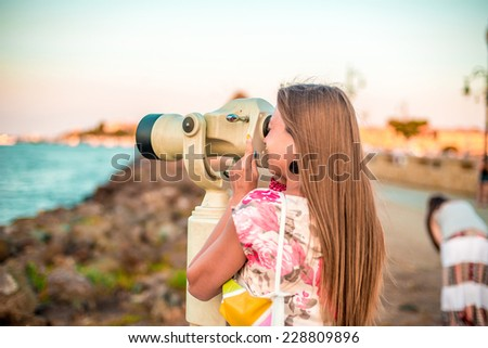 Girl with monocular looking at the evening sea landscape - stock photo