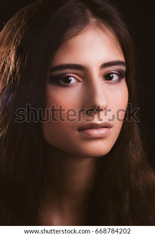 Girl with natural makeup on a black background.