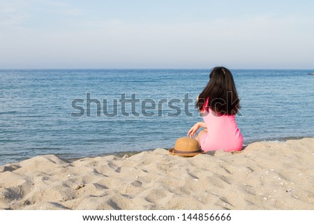Girl with neon dress plays in the beach - stock photo