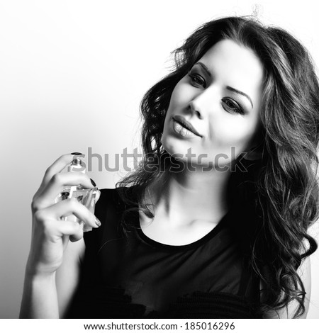 Girl with perfume, young beautiful woman holding bottle of perfume and smelling aroma, black and white. - stock photo