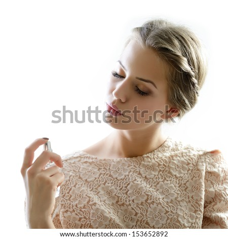 Girl with perfume, young beautiful woman holding bottle of perfume and smelling aroma, isolated on white background - stock photo