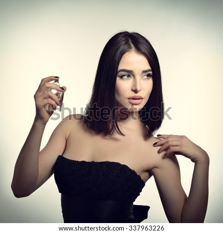 Girl with perfume, young beautiful woman holding bottle of perfume and smelling aroma, toned soft beige and noise added - stock photo
