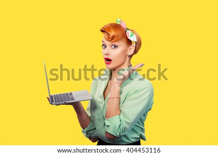 Girl with personal computer. Closeup red head beautiful young woman pretty excited, amazed smiling pinup girl green button shirt holding pc hand up looking at you camera, retro vintage 50's hairstyle - stock photo