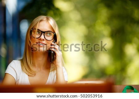 Girl with phone on background of green trees