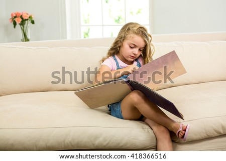 Girl with picture book while sitting on sofa