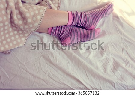 girl with pink striped socks, sleeping in bed - stock photo