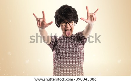 Girl with pop look making horn gesture over ocher background